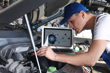 Mechanic with laptop doing car diagnostic at automobile repair shop Banco de Imagens - 150647600