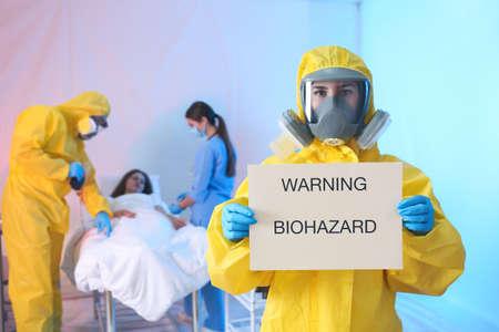 Paramedic holding sign with words WARNING BIOHAZARD in quarantine ward. Virus awareness Stock Photo