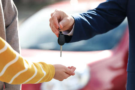 Salesman giving key to customers in modern auto dealership, closeup. Buying new car