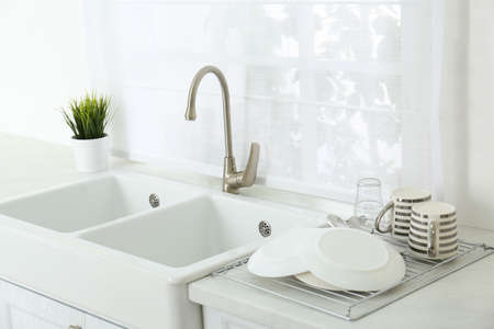 Clean dishes drying on rack in modern kitchen