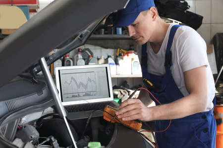 Mechanic with laptop doing car diagnostic at automobile repair shop Banco de Imagens