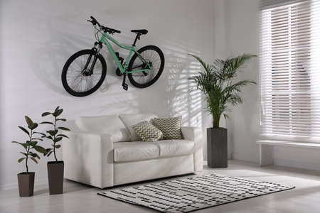 Stylish living room interior with white sofa and green bicycle