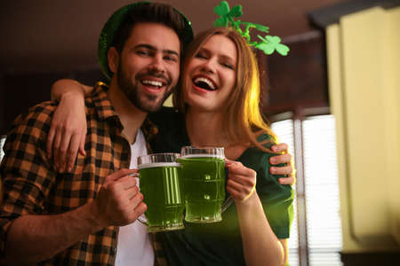 Young man and woman toasting with green beer in pub. St. Patrick's Day celebration Zdjęcie Seryjne - 143207584