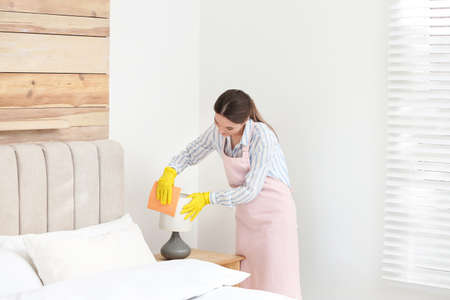 Young chambermaid wiping dust from lamp in bedroom