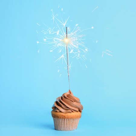 Geburtstagskuchen mit Wunderkerze auf hellblauem Hintergrund