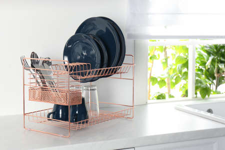 Drying rack with clean dishes on countertop in kitchen. Space for text