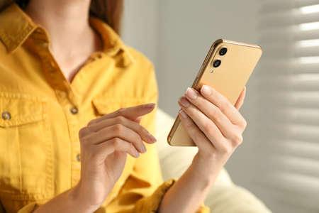 Young woman using modern smartphone indoors, closeup