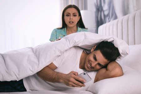 Distrustful woman peering into boyfriends smartphone at home. Jealousy in relationship