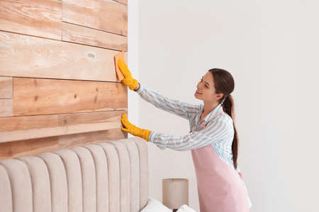 Young chambermaid wiping dust from furniture in hotel room