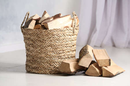 Wicker basket with cut firewood on white floor indoors