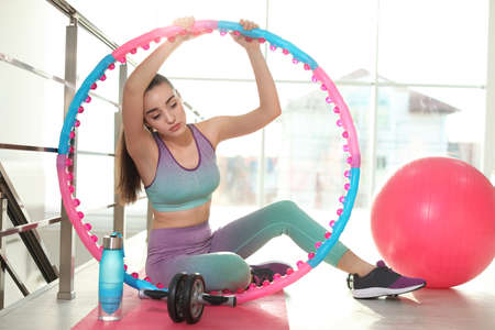Lazy young woman with sport equipment on yoga mat indoors
