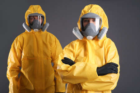 Man and woman wearing chemical protective suits on grey background. Virus research