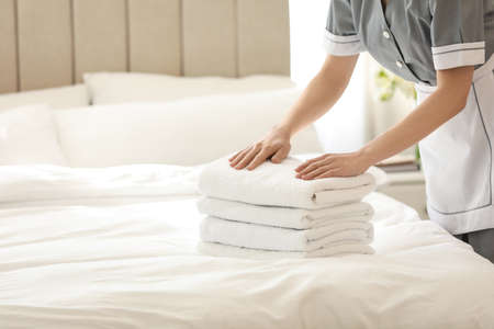 Chambermaid with stack of fresh towels in bedroom, closeup. Space for text