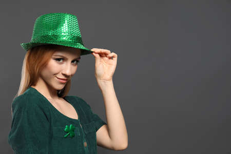 Young woman in green outfit on grey background, space for text. St. Patricks Day celebration