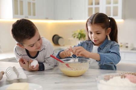 Cute little children cooking dough together in kitchen