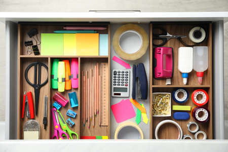 Different stationery in open desk drawer, top view Archivio Fotografico
