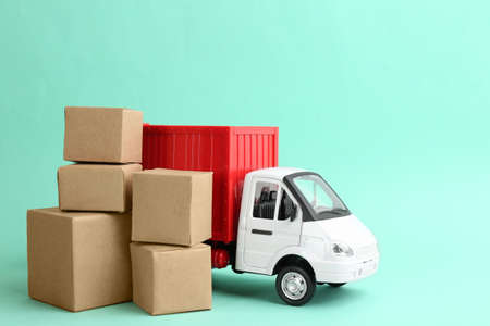 Truck model and carton boxes on turquoise background. Courier service