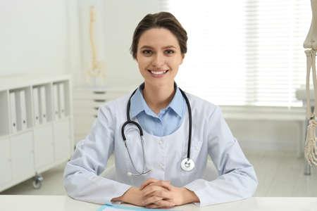 Female orthopedist at table near human skeleton model in office Stockfoto