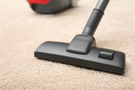 Removing dirt from carpet with vacuum cleaner indoors, closeup