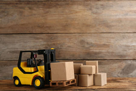 Forklift model and carton boxes on wooden background, space for text. Courier service