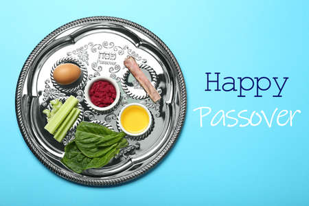 Passover Seder plate (keara) with symbolic meal on light blue background, top view. Pesah celebration