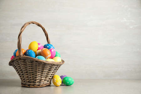 Basket with colorful Easter eggs on light grey background. Space for text Archivio Fotografico