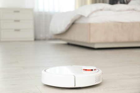 Modern robotic vacuum cleaner on floor in bedroom. Space for text Imagens
