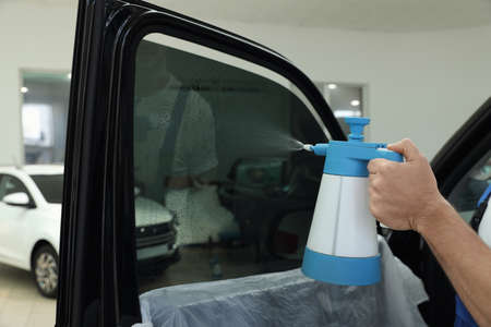 Worker spraying water onto tinted car window  in workshop, closeup