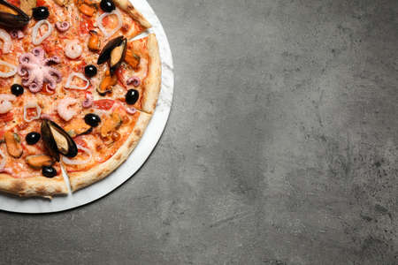 Delicious seafood pizza on grey table, top view. Space for text