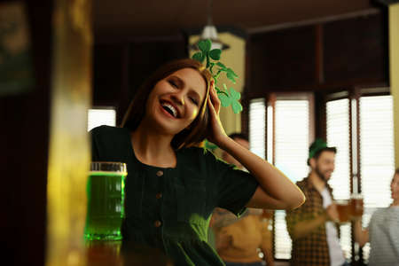 Young woman with glass of green beer in pub. St. Patricks Day celebration