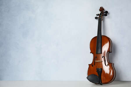 Beautiful violin on table near light blue wall. Space for text