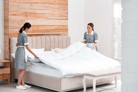 Young chambermaids making bed in hotel room