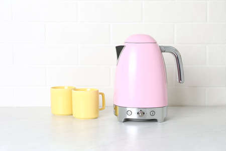 Modern electric kettle and cups on counter in kitchen