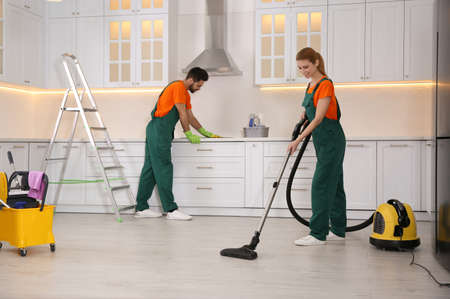 Team of professional janitors cleaning modern kitchen