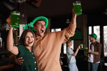Young woman and man with glasses of green beer in pub.St. Patricks Day celebration Zdjęcie Seryjne
