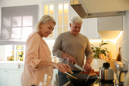 Mature couple cooking food together in kitchen