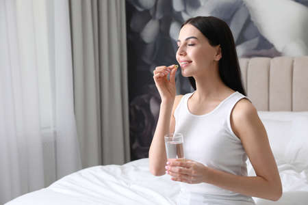 Woman with glass of water taking vitamin capsule in bedroom. Space for text