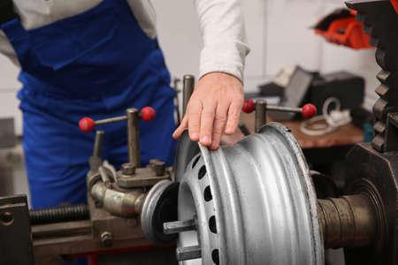 Mechanic working with car disk lathe machine at tire service, closeup Standard-Bild