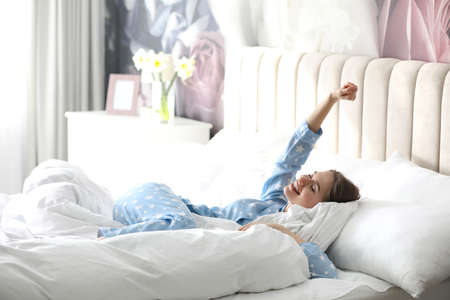 Young woman lying on comfortable pillow in bed at home