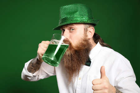 Bearded man drinking green beer on color background. St. Patricks Day celebration