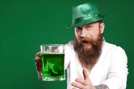 Bearded man with green beer on color background. St. Patrick's Day celebration Zdjęcie Seryjne - 143131558