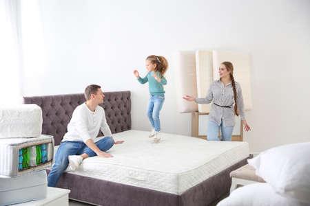 Happy family choosing mattress in furniture store Imagens