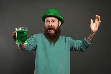 Bearded man with green beer on grey background. St. Patrick's Day celebration Zdjęcie Seryjne - 143131312