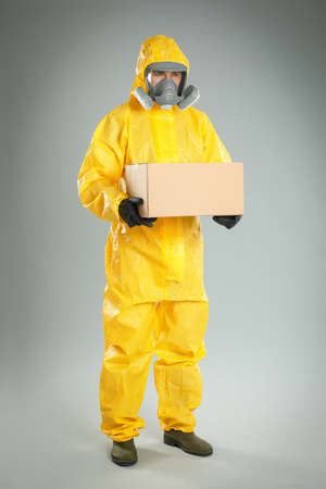 Man wearing chemical protective suit with cardboard box on light grey background. Prevention of virus spread