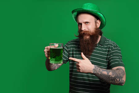 Bearded man with green beer on color background. St. Patricks Day celebration