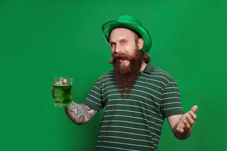 Bearded man with green beer on color background. St. Patrick's Day celebration Zdjęcie Seryjne - 143131326