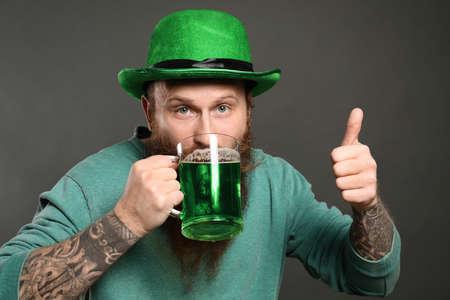 Bearded man drinking green beer on grey background. St. Patricks Day celebration Zdjęcie Seryjne