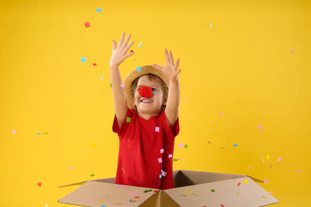 Little boy with clown nose in cardboard box under confetti shower on yellow background. April fool's day