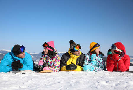 Group of friends lying on hill. Winter vacation