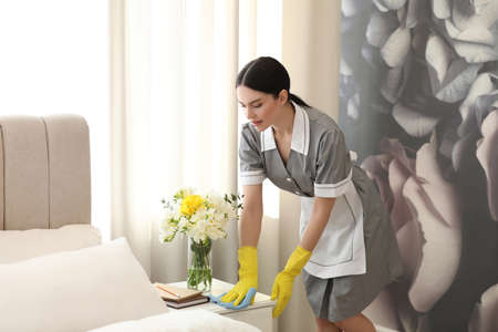 Young chambermaid wiping dust from nightstand in bedroom Imagens